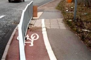 Image of a cycle path painted on a road with a metal fence running the length of it, dividing it in half