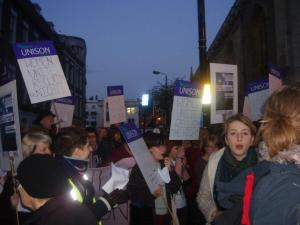 Group of women marching with placards reading 'Women Unite Reclaim the Night'